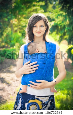 mother with newborn baby in a sling