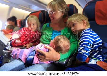 mother with newborn baby, little son and daughter travel by plane