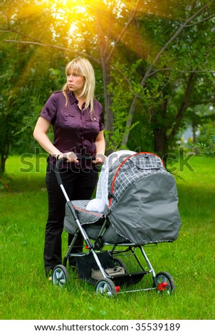 mother with pram walking in a city park