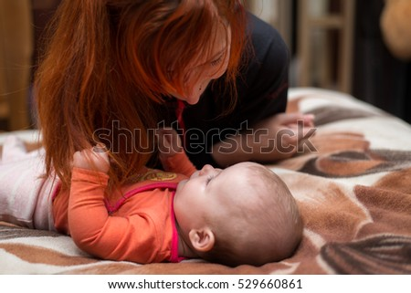 mother with red hair playing a child, happy and smiling