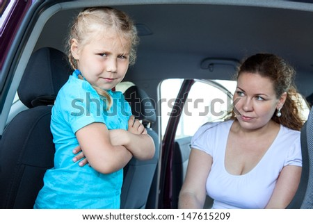 Mother with small child sitting in land vehicle against girl`s wishes - stock photo