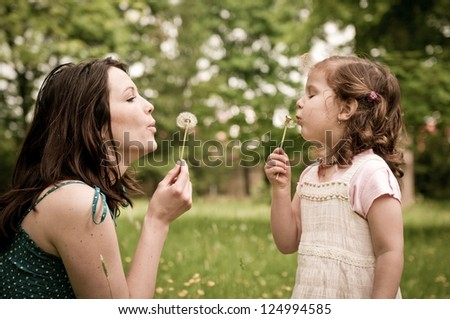 Mother with small daughter blowing to dandelion - lifestyle outdoors scene in park - stock photo