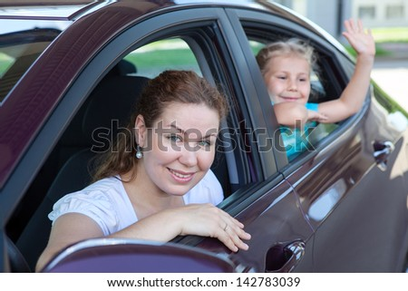 Mother with small daughter sitting in own car and waving at camera - stock photo