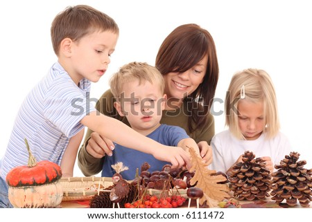mother with son and daughter making autumn decoration isolated on white
