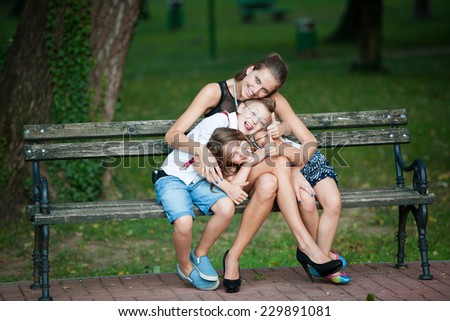 Mother with son and daughter on a walk in park in late summer afternoon - stock photo