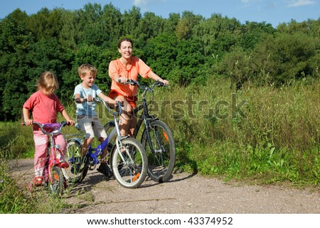 Mother with son and daughter ride bikes outside the city - stock photo