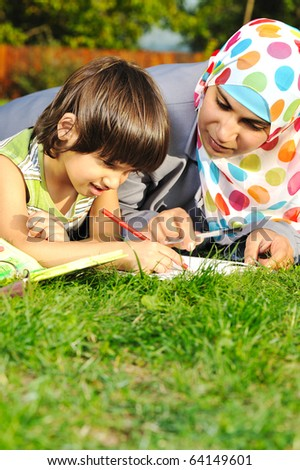 Mother with son, education in nature, laying on grass with notebook - stock photo