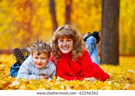 mother with son in the autumn park lying on the grass