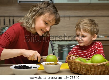 Mother with son is eaten fruit in kitchen - stock photo