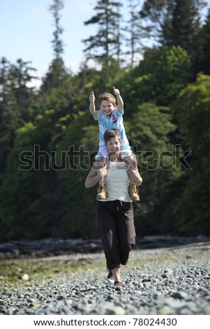 mother with son on her shoulders at a beach - stock photo