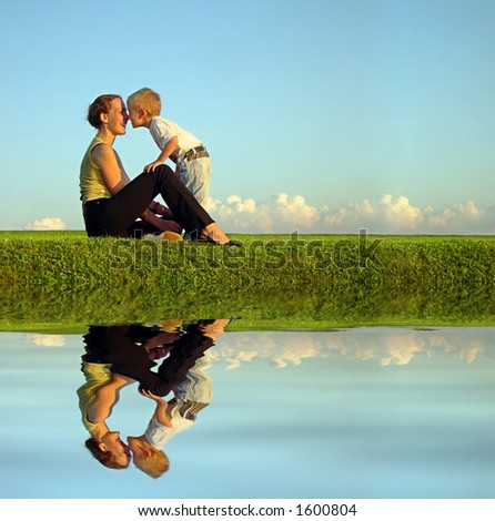 mother with son on sundown kiss by nose. long. water - stock photo