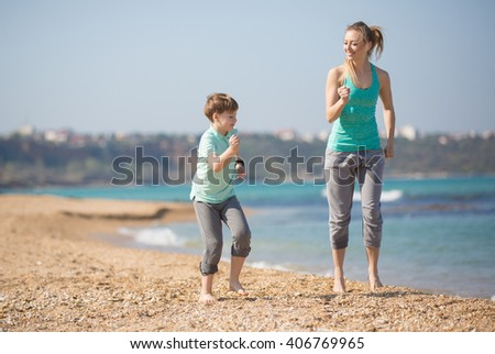 Mother with son running on the beach at morning