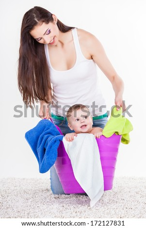 Mother with Son Sitting In Laundry Basket on white. Family, adorable kid, love and happiness concept. - stock photo