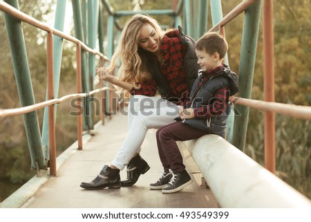 Mother with son sitting on a bridge in sunny day