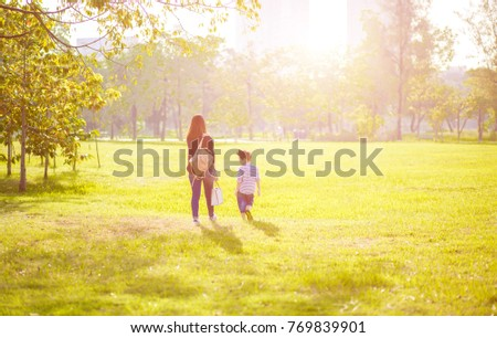Mother with son walking in the field. Happy family life style concept.