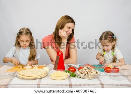 Mother with tenderness looks like her little daughter to help her in the kitchen to prepare meals