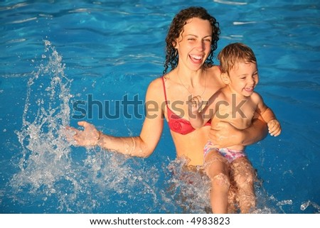 mother with the child in the water - stock photo