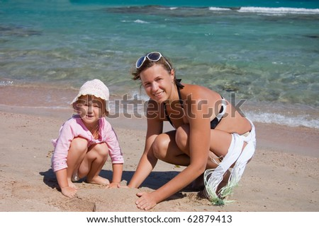 mother with the child playing with sand on beach