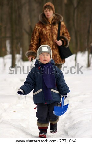 Mother with the child walk in winter park - stock photo