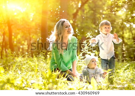 mother with the daughter and the son on a summer glade have a rest and have fun - stock photo