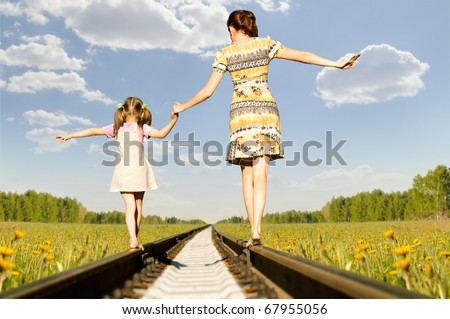 Mother with the daughter go on rails,  back to a camera, on nature, in the summer - stock photo