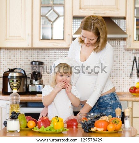 mother with the daughter make a dinner in kitchen - stock photo