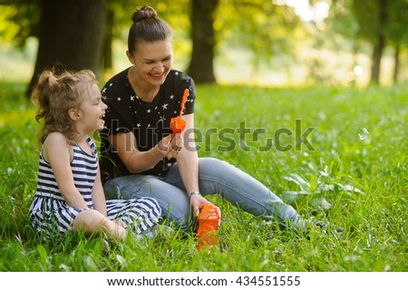 Mother with the daughter sit on a grass in park and are going to start up soap bubbles. They have a good mood and they laugh. In an environment of bright greens of park.