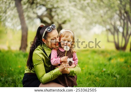 mother with the little daughter blow on a dandelion  in warm sunny spring day in the park - stock photo