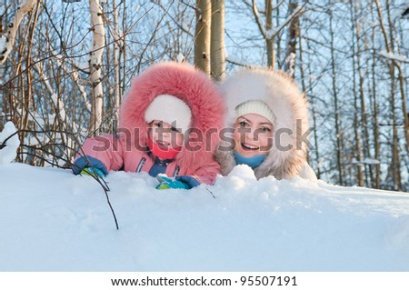 Mother with the small daughter walk in winter wood. - stock photo