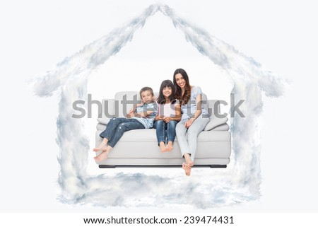 Mother with their children sitting on sofa against house outline in clouds - stock photo