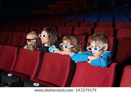Mother with their children watching a movie in 3D glasses in the cinema - stock photo