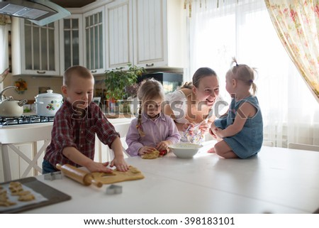 mother with three children in the kitchen preparing cookies, large family. casual lifestyle photo series in real life interior - stock photo