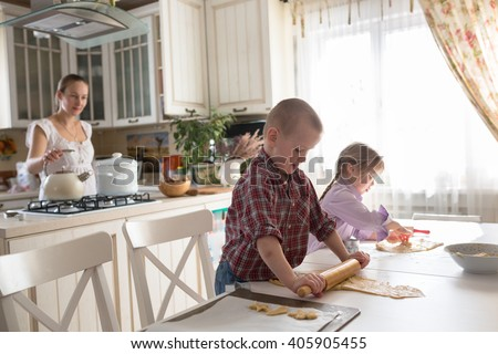 Mother with three kids cooking biscuits  in the kitchen, casual lifestyle photo series in real life interior - stock photo