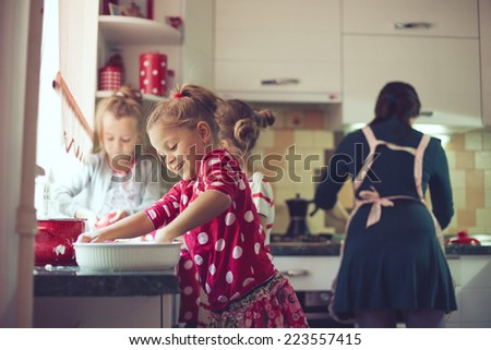 Mother with three kids cooking holiday pie in the kitchen, casual lifestyle photo series in real life interior - stock photo