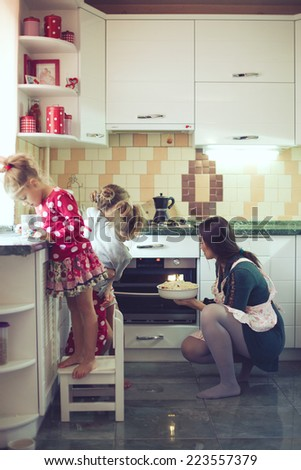 Mother with three kids cooking holiday pie in the kitchen to Mothers day, casual lifestyle photo series in real life interior - stock photo