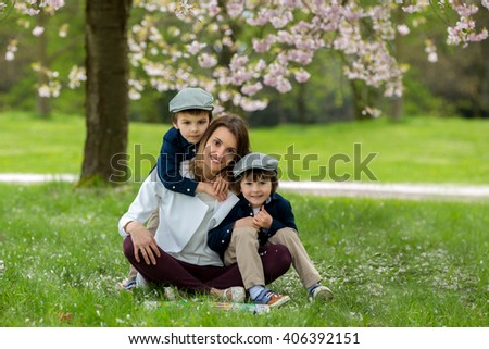 Mother with two children, boys, reading a book in a cherry blossom garden, springtime - stock photo