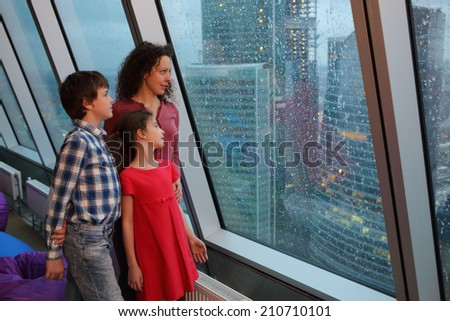 Mother with two children looking at evening city through a large window - stock photo