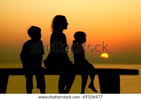 Mother with two children sits on  bench and looks at  beach toward sunset - stock photo