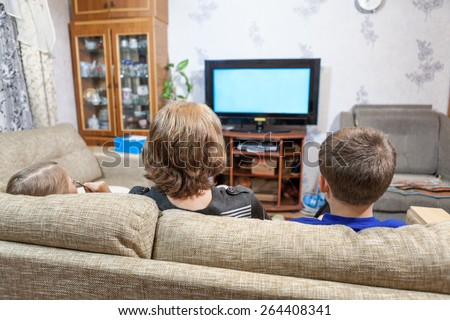 Mother with two children sitting on couch and watching tv at home - stock photo