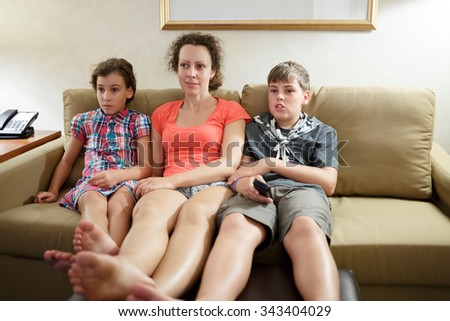 mother with two children watching tv on a coach - stock photo