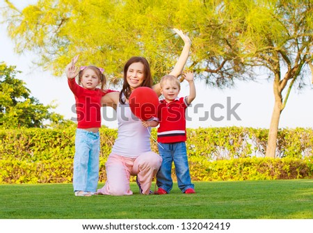 Mother with two cute kids raising hands up and enjoying sunny day, happy young family waving hand in spring park, woman with daughter and son having fun outdoors, happiness concept - stock photo