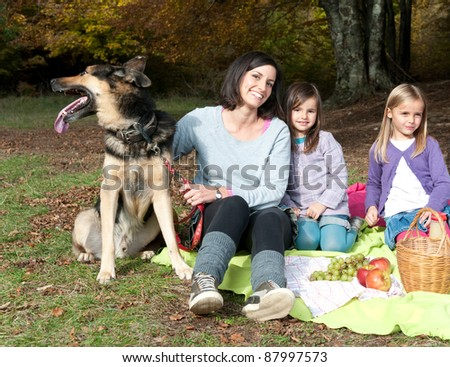 Mother with two daughters and a dog on picnic in forest - stock photo