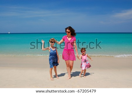 Mother with two daughters on the beautiful tropical beach