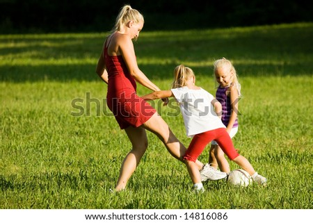 Mother with two daughters playing football (well, soccer for North America) on a green, sunlit meadow - stock photo