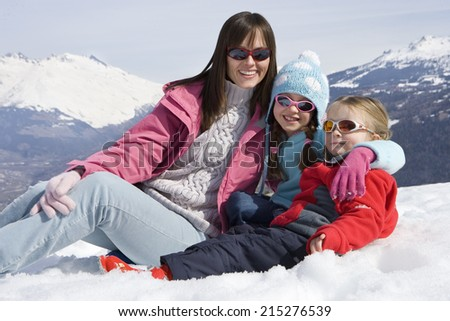 Mother with two daughters (6-8) sitting together in snow field, wearing sunglasses, smiling, portrait, mountain range in background