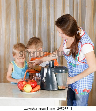 Mother with two kids doing juice from juicing machine at kitchen - stock photo