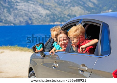 mother with two kids travel by car on sea vacation - stock photo