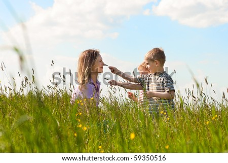 Mother with two little boys playing in the grass on a summer meadow