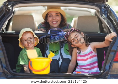 Mother with two little children sitting in the back seat, traveling on summer vacation. - stock photo