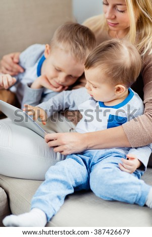 Mother with two sons playing with digital tablet together. Two boys looking at screen - stock photo